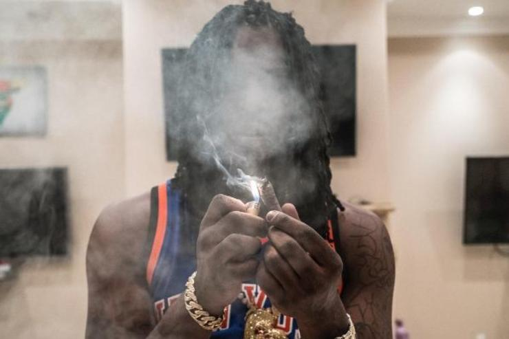 Chief Keef lights a blunt.