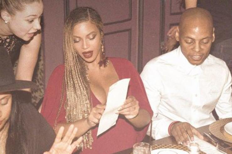 Beyonce stares at a menu in a restaurant.
